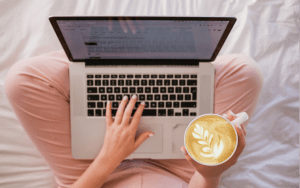A woman with white painted fingernails sits on a duvet crossed legged. Her laptop is resting on her knees, while one hand types on her MacBook and the other holds a cup of Latte style coffee.